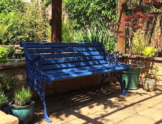 Blue garden bench in dappled shade