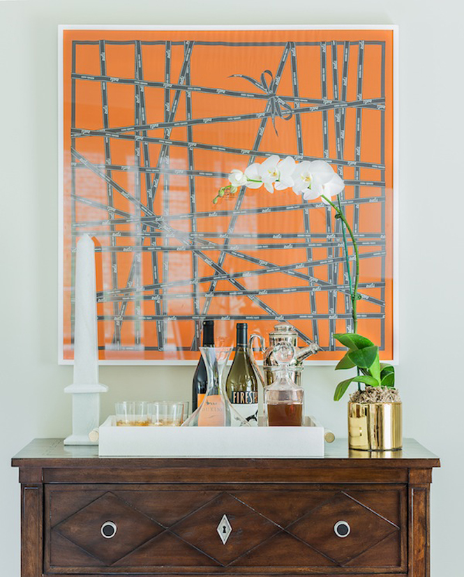 Framed orange Hermes scarf above bar