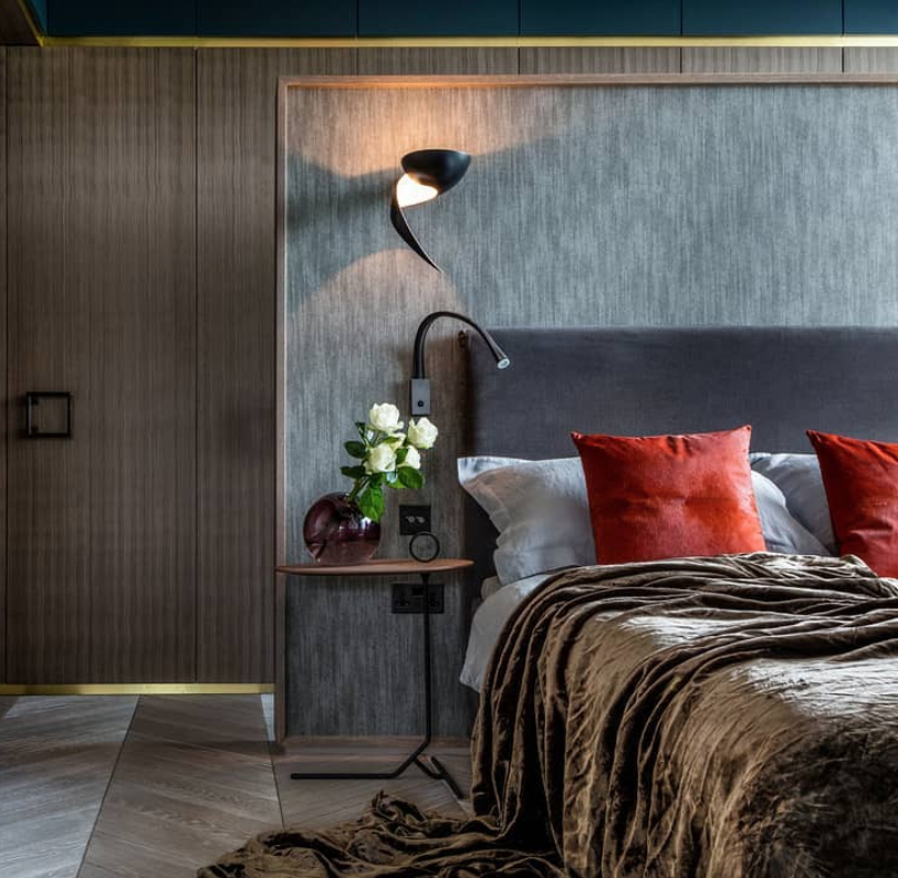 Luxe bedroom with a feature wallpapered wall behind bed