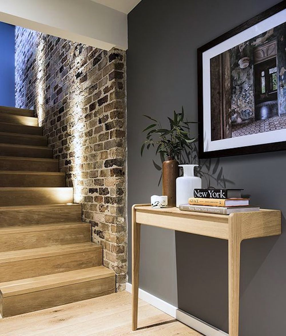Staircase with brick accent wall