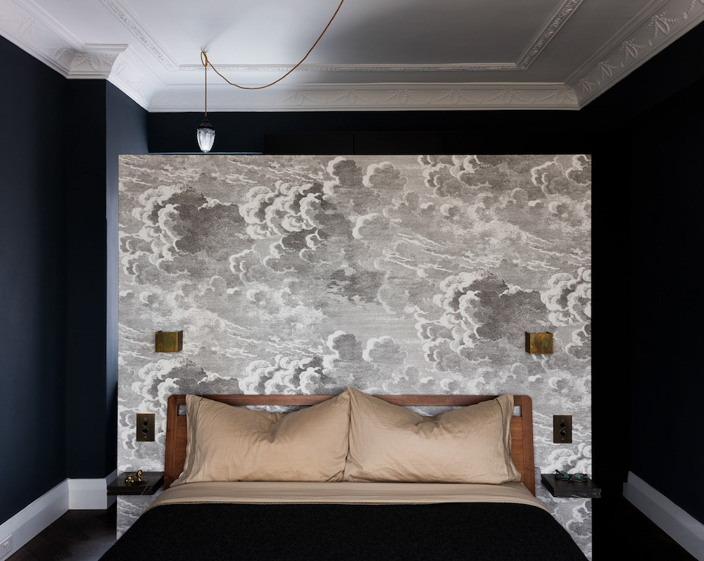 Wallpapered false wall in bedroom frames the bed