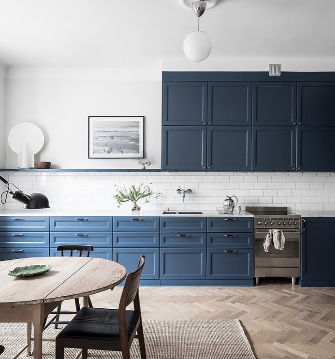 Blue and white kitchen diner with parquet wood floor