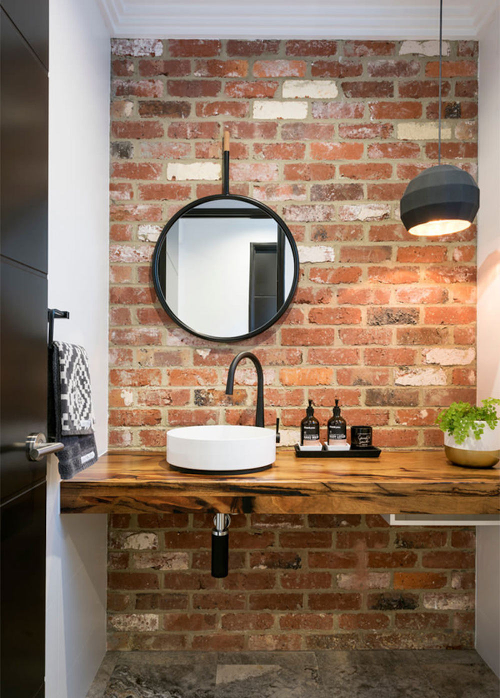 Small bathroom with exposed brick wall