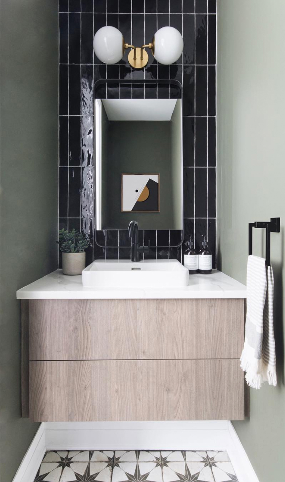 Sage green powder room with black tiles // Leclair Decor