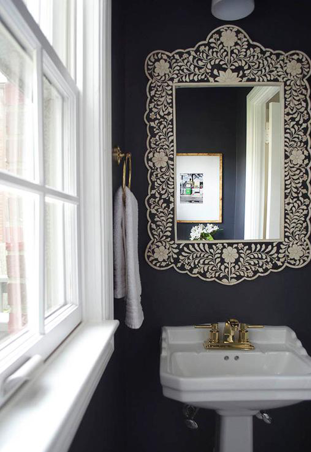 Dark powder room with statement bone inlay mirror || 15 small cloakrooms / powder rooms that are big on style - FIRST SENSE