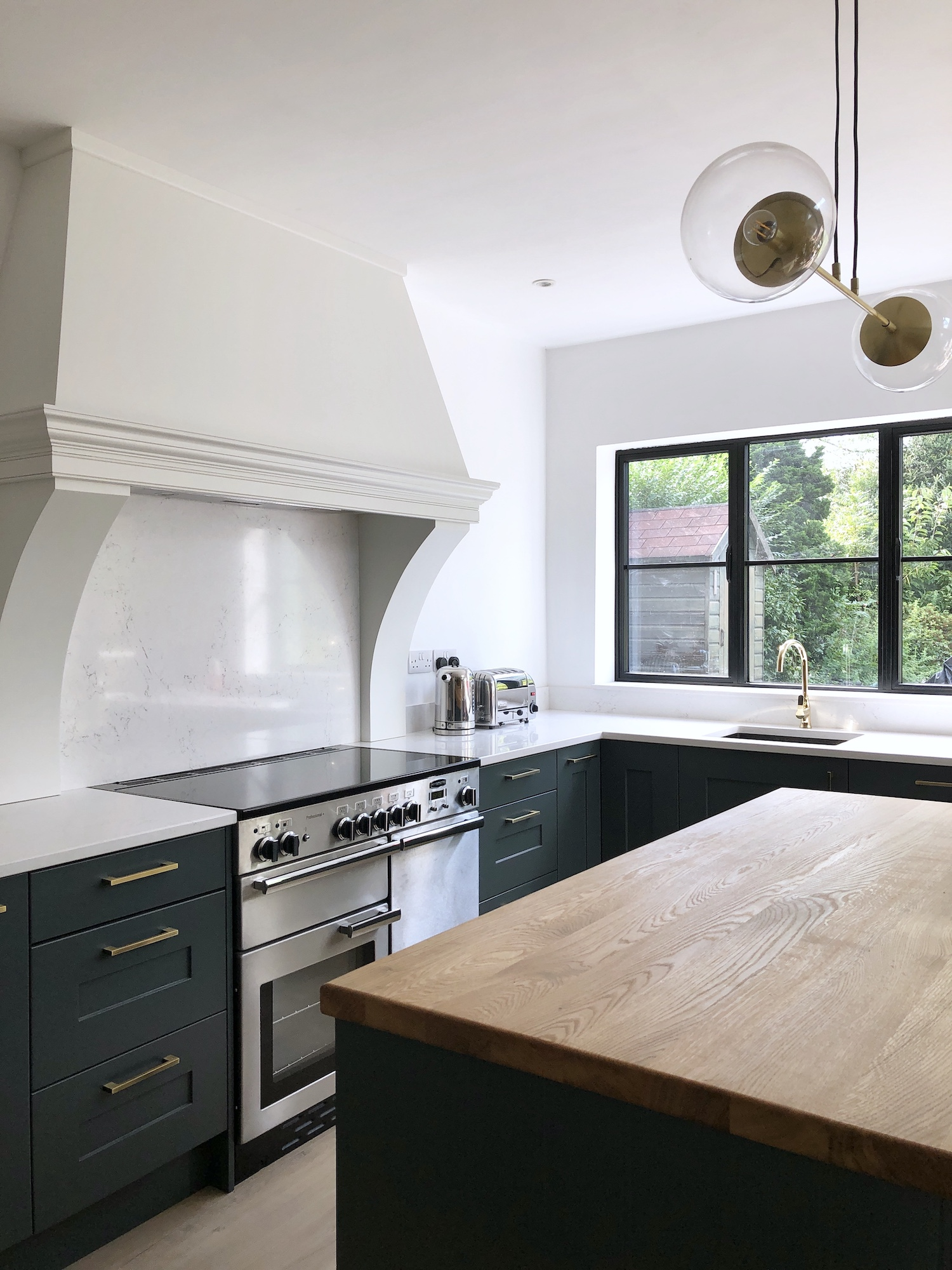 First Sense Interiors - Blue Shaker kitchen with quartz and oak worktops and a custom built extractor chimney hood