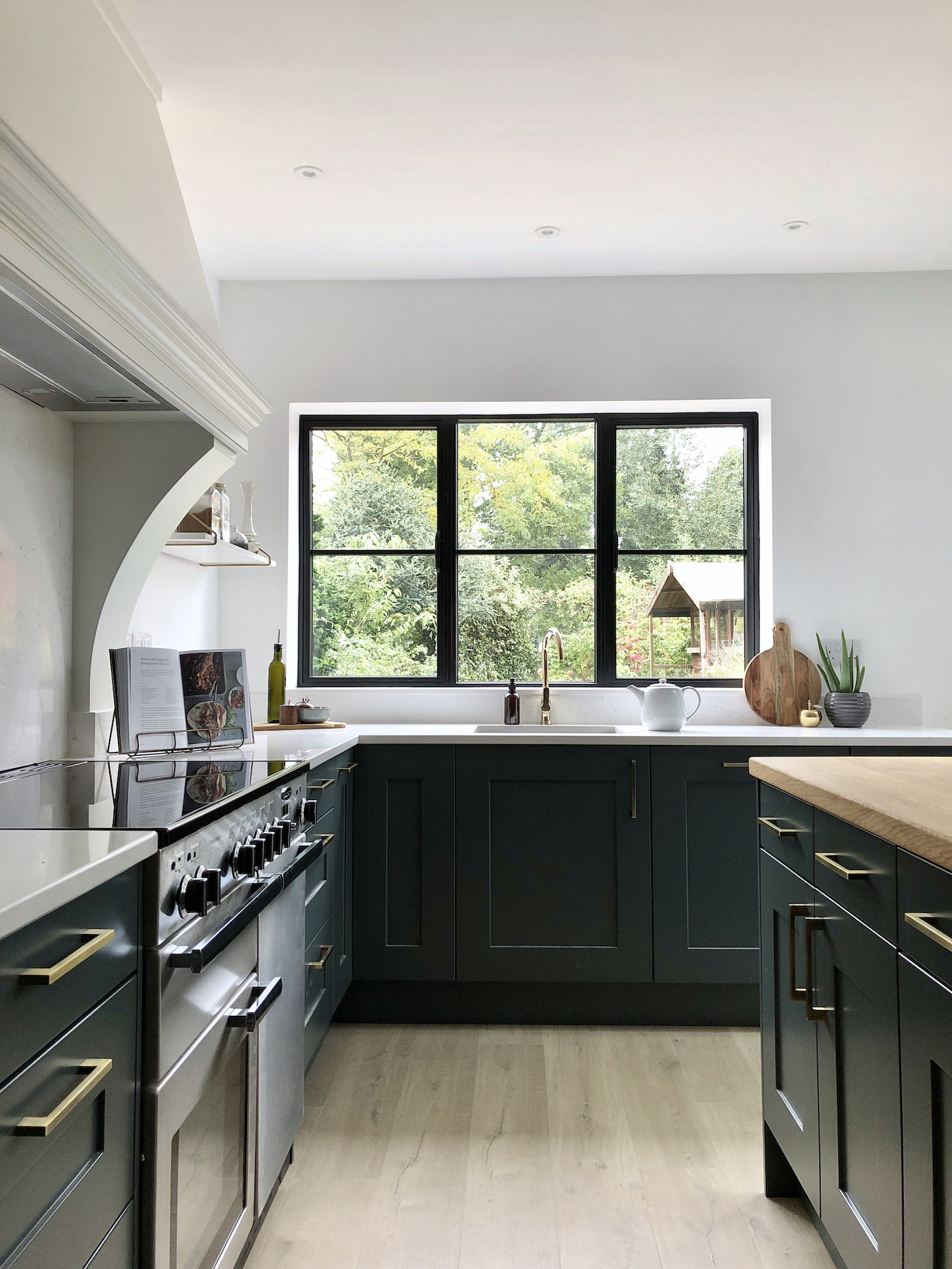 First Sense Interiors - Dark Blue Green Shaker kitchen with quartz and oak worktops and a custom extractor chimney hood