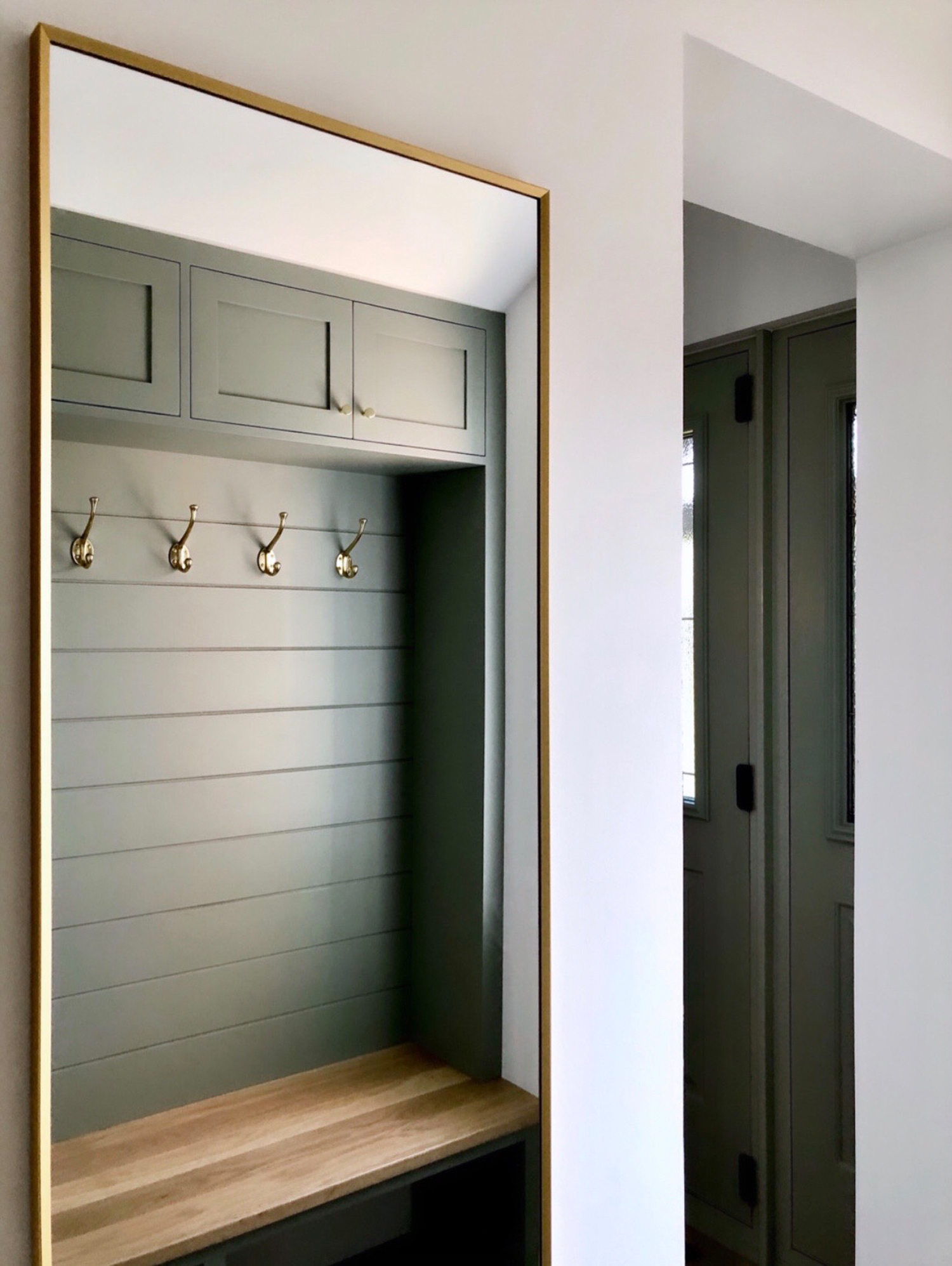 Custom boot room painted in Farrow & Ball Pigeon with a solid oak seat and brass hardware - design by First Sense Interiors