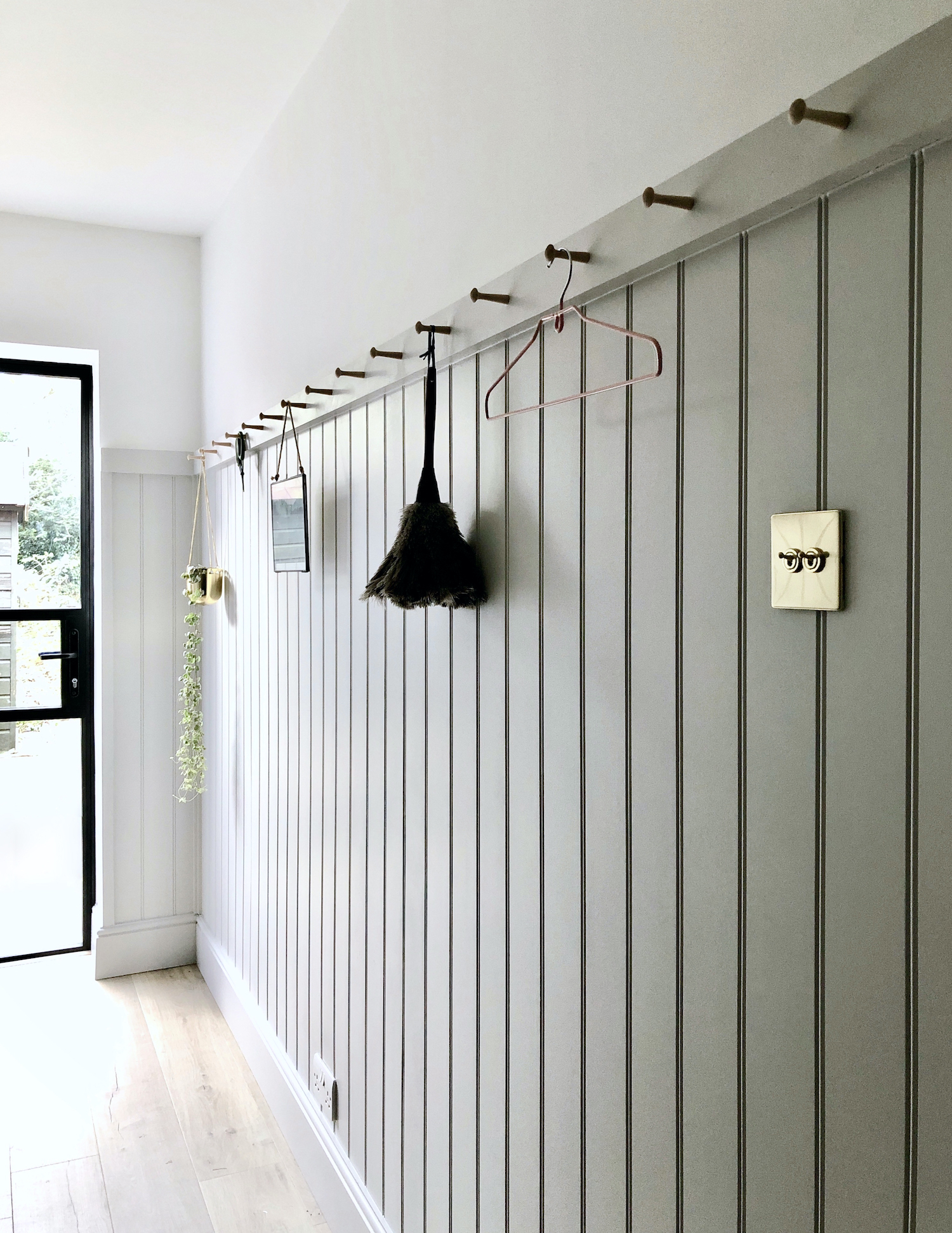 Utility laundry room design with peg rail and black aluminium glazed door. Design by First Sense Interiors